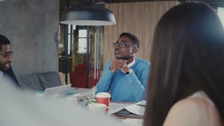 Handsome African American young manager discussing work with multiethnic colleagues at team meeting in modern office 4K.