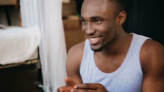 Handsome african man throws the dice, laughs and takes the card. Multiethnic couple playing the board game.