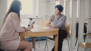 Handsome Asian man talking to female life coach by the table. Multiethnic people talk in stylish modern coworking 4K.
