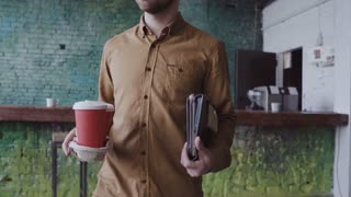 Handsome business man comes to modern office at work. Young male greets with colleagues, brings coffee to friend slow mo