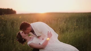 Handsome groom holds his beautiful bride in his arms, kissing her. She laughs. Wedding at sunset in a beautiful place