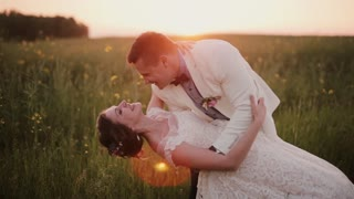 Handsome groom holds his beautiful bride in his arms, kissing her. Wedding at sunset in a beautiful place in nature
