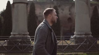 Handsome man walks on ruins of Rome, Italy. Guy does up hair, explores the architecture of Roman forum. Slow motion.