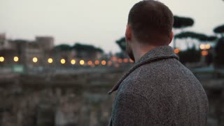 Handsome tourist man stands back to the camera considering the sights in the centre of Rome in Italy. Slow motion