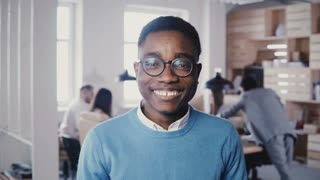 Handsome young African American businessman in glasses smiling at camera. Hipster stylish male office worker posing 4K.