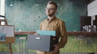 Handsome young man getting fired from work. Sad male walks through the office, carrying box with personal belongings.
