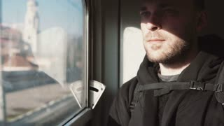 Handsome young man traveling by train. Attractive male looking at window and thinking, sitting in the shadow.