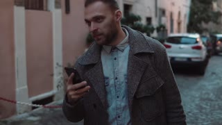 Handsome young man walks alone in evening, uses smartphone. Stylish male exploring old town part of city. Slow motion.