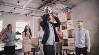 Happy African American boss juggles ball on head. Multiethnic business people celebrate success in office slow motion