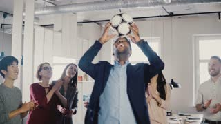 Happy African American CEO juggling ball on head. Multi ethnic business executive people celebrate success in office 4K.
