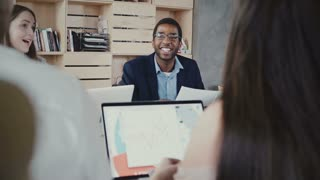 Happy African American company boss laughs at multiethnic office meeting, then goes serious again in trendy coworking 4K