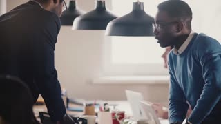 Happy African American employee sits on office table, shakes boss hand, smiling, playing with ball slow motion close-up.