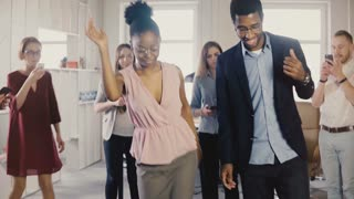 Happy African American friends doing ethnic dance at office party. Multiethnic business people share fun time at work 4K