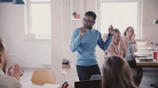 Happy African American male team leader doing silly winner dance in multiethnic loft office, colleagues clap slow motion