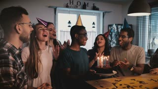 Happy African American man holding birthday cake, dancing and celebrating at multiethnic party with friends slow motion.