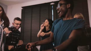 Happy African American young man dancing together with friends at casual multiethnic house party celebration slow motion