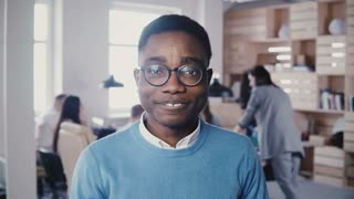 Happy African American young office worker in glasses staring at camera. Stylish graphic designer posing and smiling 4K.