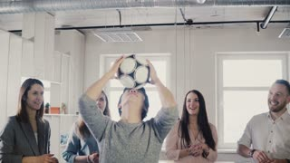 Happy Asian man tries to juggle football on head. Positive mixed ethnicity workers play fun sports game in office 4K