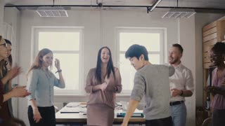 Happy Asian young businessman dancing at casual office party. Japanese employee celebrates victory with colleagues 4K.