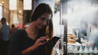 Happy attractive female CEO using smartphone e-commerce app near steaming street food vendor in evening New York City.