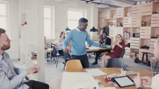 Happy black man doing funny victory dance celebrating achievement. Multiethnic colleagues clapping in modern office 4K.