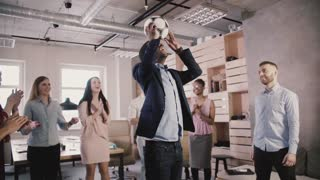 Happy black team leader juggles football on head. Multiethnic startup employees celebrate success in office slow motion