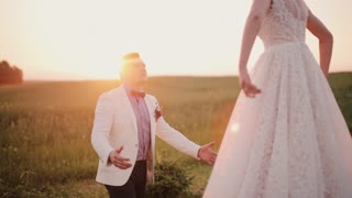 Happy bride jumps into her grooms arms, he catches her and swirls around in a field at sunset. Wedding on a summer day.