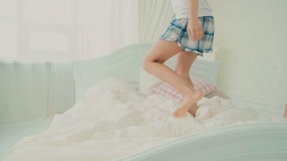 Happy brunette woman in pajamas jumping on white bed in morning and smiling. Beautiful girl having fun. Slow motion