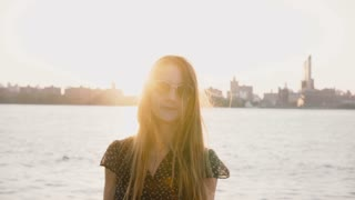 Happy casual Caucasian girl in fashionable sunglasses posing at camera, NYC sunset skyline and river in background 4K.