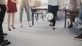 Happy casual workers play with ball in office. Young multiethnic employees celebrating business success with activity 4K