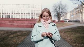 Happy Caucasian 30s woman typing on smartphone. Pretty stylish blonde texting while walking in the city. Slow motion.