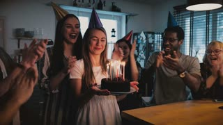 Happy Caucasian girl holding birthday cake, making a wish at cheerful fun multiethnic party with friends slow motion 4K.