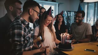Happy Caucasian girl makes a wish at birthday cake with candles. Multiethnic friends at surprise party slow motion.