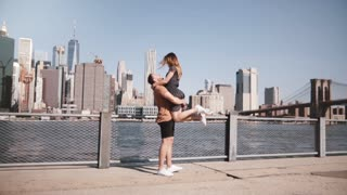 Happy Caucasian man holding his girlfriend in arms smiling at famous Brooklyn Bridge view in New York slow motion.