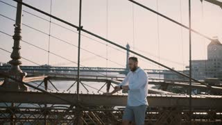 Happy Caucasian man stands alone at Brooklyn Bridge looking away and using smart watch bracelet on a sunny summer day 4K