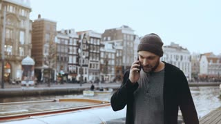 Happy Caucasian man walks and talks on the phone. 4K. Excited creative tourist sharing emotions in Amsterdam old town.