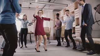 Happy Caucasian woman leader dancing at casual office party. Multiethnic business people celebrate success slow motion.