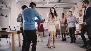 Happy CEO businesswoman celebrating corporate achievement with a dance at casual multiethnic office party slow motion.