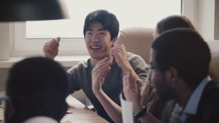 Happy confident Japanese young freelance businessman sharing ideas, smiling at multiethnic office meeting slow motion.
