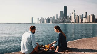 Happy couple enjoying beautiful landscape of Chicago, America on the shore of Michigan lake during picnic.