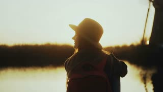 Happy cute girl in hat sits on sunset river pier. Golden hour. Enjoying wonderful travel moment. 4K back view close-up.
