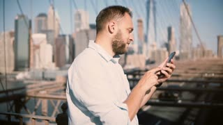 Happy European businessman using smartphone mobile office app at Brooklyn Bridge, then turning away from camera 4K.