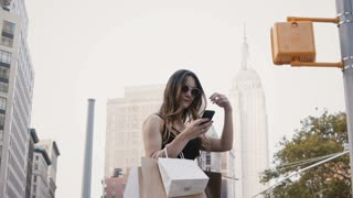 Happy European female freelance worker with shopping bags in sunglasses smiling, using smartphone app in New York City.