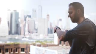 Happy European freelance worker smiling, using smart watch to shop online at amazing Manhattan skyline, New York City.
