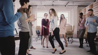 Happy European girl doing moonwalk dance at fun office party. Multiethnic business people celebrate success slow motion.