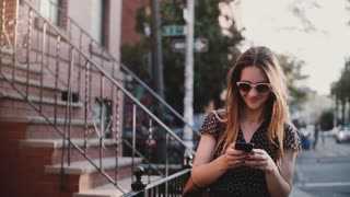 Happy European girl with long hair smiling, walking along old big red brick buildings, using smartphone app slow motion.