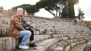 Happy European senior man and young woman sitting on old amphitheater ruins in Ostia, Italy with a map and smartphone.