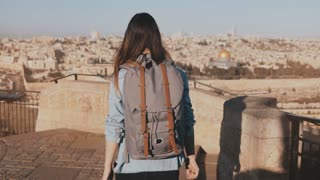 Happy European tourist female raises hands. Israel, Jerusalem. Girl with backpack walks to see old town panorama. 4K.