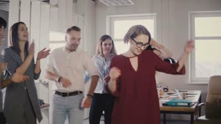 Happy European woman leader dancing at office party. Multiethnic colleagues enjoy fun bonding time activity together 4K.