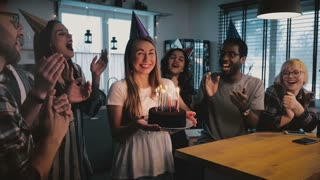 Happy excited Caucasian girl holding birthday cake, multiethnic friends sing a cheerful song at fun party slow motion.